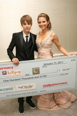 "Justin Bieber presents a check from CVS Pharmacy to Maria Menounos for The Lollipop Theater Network and Best Buddies charities as part of Access' ""Stuff You Must"" lounge --"