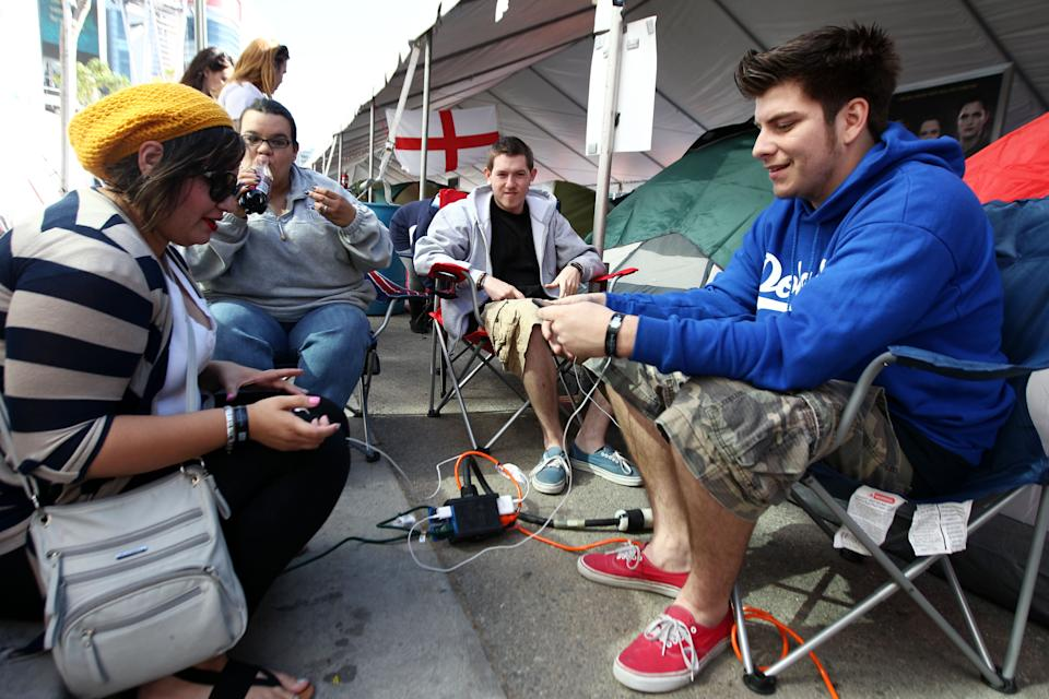 "Fans sit around a charging station at the Twilight fan camp ahead of the world premiere of ""The Twilight Saga: Breaking Dawn - Part 2"" on Friday, Nov. 9, 2012 in Los Angeles. The premiere will be held Nov. 12, 2012. (Photo by Matt Sayles/Invision/AP)"