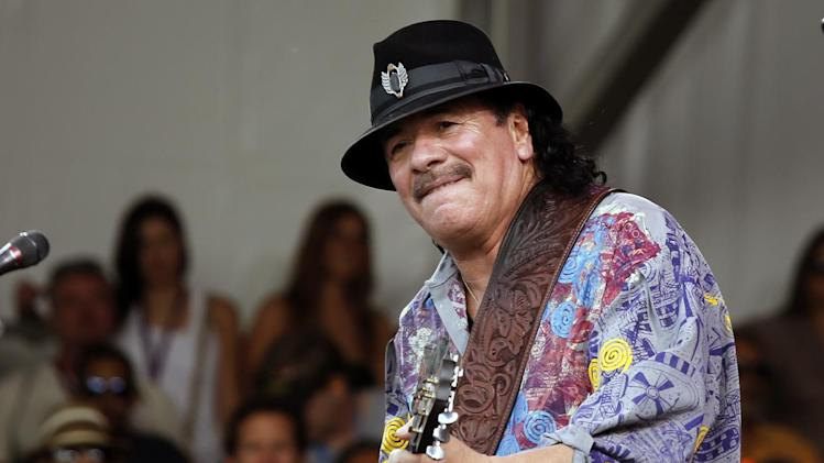 "FILE - This April 25, 2014 file photo shows Carlos Santana performing during the New Orleans Jazz and Heritage Festival in New Orleans. Santana's latest album, ""Corazon,"" debuted at No. 9 on the Billboard 200 albums chart last week. It features Juanes, Gloria Estefan and Miguel, and Santana said it wasn't hard finding ""Cinderella or Cinderfella"" to guest on the songs, which he calls ""glass slippers."" (AP Photo/Doug Parker, File)"