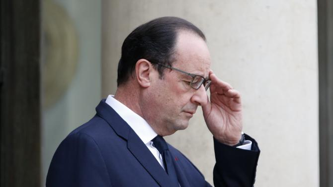 French President Francois Hollande adjusts his glasses as he waits for a guest on the steps of the Elysee Palace in Paris