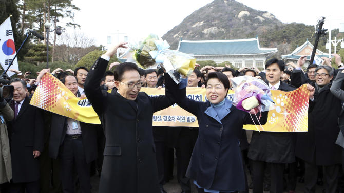South Korea's outgoing President Lee Myung-bak, left, and his wife Kim Yoon-ok, right, make heart shape with arms before leaving the presidential Blue House in Seoul, South Korea, Sunday, Feb. 24, 2013. Park Geun-hye will take office Monday, Feb. 25 as South Korea's first female president. (AP Photo/Yonhap, Do Kwang-hwan) KOREA OUT