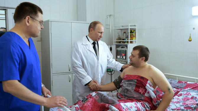 Russian President Vladimir Putin, center, greets a victim of recent terrorist attacks as he visits a hospital in Volgograd, Russia, Wednesday, Jan. 1, 2014. Putin on Wednesday made a pre-dawn visit to the city reeling from two suicide bombings this week, bringing gestures of sympathy for the victims and questions for the officials he has ordered to beef up security. (AP Photo/RIA-Novosti, Alexei Nikolsky, Presidential Press Service)