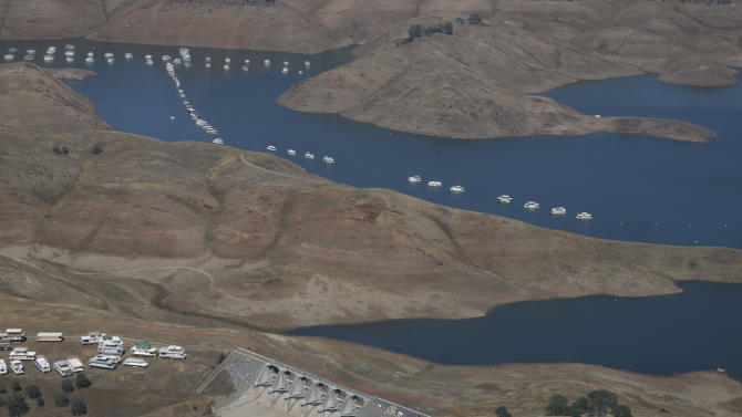 In this aerial photo taken Tuesday, April 28, 2015, a spillway sits more than a 100 yards away from the water level of New Hogan Lake  near Valley Springs, east of Lodi, Calif. The State Water Resources Control Board is considering sweeping mandatory emergency regulations to protect water supplies as water levels at some of California's lakes and reservoirs continue to decline.(AP Photo/Rich Pedroncelli)