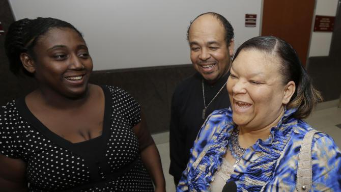 Auboni Champion-Morin, left, laughs with Juanita, right, and Joesph Aguillard after a court hearing regarding Champion-Morin's son Wednesday, Jan. 9, 2013, in Houston. A judge in Houston ruled Wednesday that 8-year-old Miguel Morin, a Texas boy who was kidnapped as a baby, should be removed from foster care and given to the Aguillard's, who are caring for his four siblings. The boy has been in foster care since authorities found him in March living in East Texas with his former baby sitter. The boy's former baby sitter and her mother are charged with kidnapping.(AP Photo/David J. Phillip)