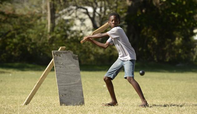 Boy plays a shot during a cricket match with friends at Belleplaine