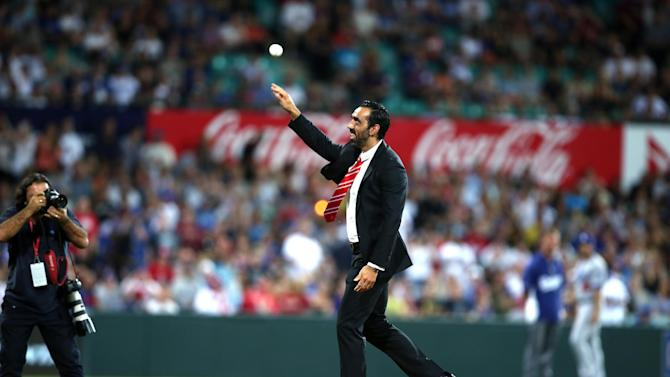 FILE - In this March 22, 2014 file photo, Australian of the year AFL player Adam Goodes throws out the ceremonial first pitch before the Major League Baseball opening game between the Los Angeles Dodgers and the Arizona Diamondbacks at the Sydney Cricket ground in Sydney. Australians tend to laud their champions, so the fact that crowds continue to loudly boo him when he plays for the Sydney Swans in the nation-wide Australian Football League has both concerned and confounded Goodes to the point where he's considering retirement. (AP Photo/Rick Rycroft, File)