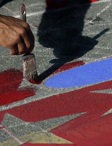 Agnaldo Eduardo Kobra, of Brazil, works on his 3D pavement art during the Sarasota Chalk Festival Wednesday, Oct. 31, 2012, in Sarasota, Fla. The annual festival begins this week and runs through Nov. 6.(AP Photo/Chris O'Meara)