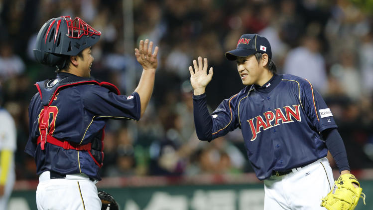 Japan's reliever Kazuhisa Makita, right, celebrates with catcher Shinnosuke Abe after defeating Brazil 5-3 in their World Baseball Classic first round game in Fukuoka, Japan, Saturday, March 2, 2013. (AP Photo/Koji Sasahara)