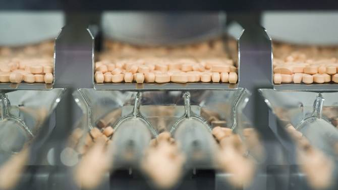 In this July 12, 2012, photo, Centrum multivitamins are shown on the packaging line at the Pfizer plant in Montreal. Drugmaker Pfizer's third-quarter profit falls 14 percent as sales plunge amid increased generic competition to cholesterol fighter Lipitor, long the world's top-selling drug. Its sales dove 71 percent to $749 million.   (AP Photo/The Canadian Press, Graham Hughes)