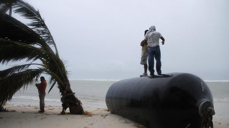 Men stand on top of a marine fender that was ripped from a dock after Hurricane Ernesto made landfall overnight in Mahahual, near Chetumal, Mexico, Wednesday, Aug. 8, 2012. (AP Photo/Israel Leal)
