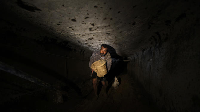 A Palestinian cleans a tunnel in Rafah, on the border between Egypt and the southern Gaza Strip, Thursday, Feb. 19, 2013. The Gaza Strip's Hamas government and local smugglers accused Egypt Tuesday of flooding cross-border tunnels with sewage water in order to halt a thriving smuggling trade that has helped prop the local economy for more than five years. (AP Photo/Hatem Moussa)
