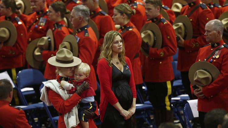 Rachael, the widow of RCMP K-9 officer David Ross, one of three officers who were killed last week, arrives with their son Austin at a regimental funeral Moncton250