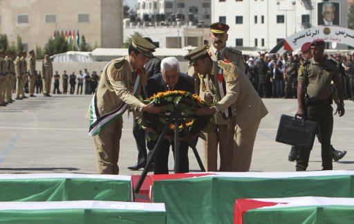 Palestinian President Abbas lays a wreath in front of coffins containing the remains of Palestinian militants during an ceremony in Ramallah