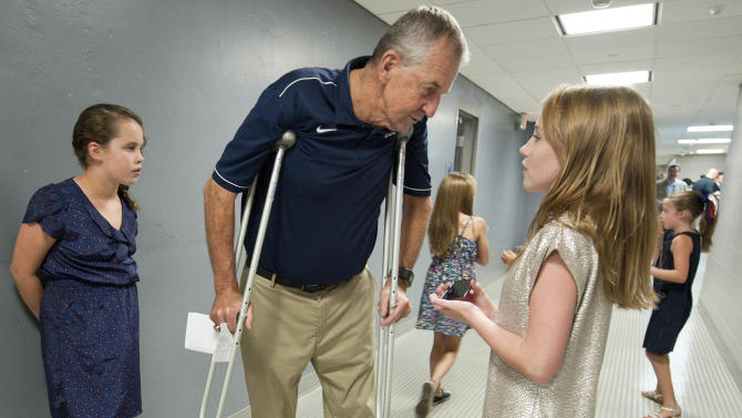 Retired Connecticut head coach Jim Calhoun, center, meets with his granddaughters Avery Calhoun, left, and Emily Calhoun after a news conference in Storrs, Conn., Thursday, Sept. 13, 2012. The 70-year-old Hall of Famer who ran the men's program for 26 years and won three national titles announced his retirement on Thursday. (AP Photo/Jessica Hill)