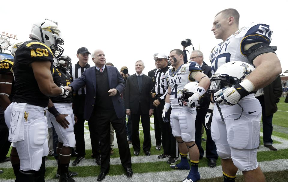 Sen. John McCain, R-Ariz., center, shakes hands with Navy and Arizona State players before the start of the Fight Hunger Bowl NCAA college football game in San Francisco, Saturday, Dec. 29, 2012. (AP Photo/Marcio Jose Sanchez)