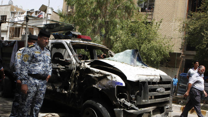 CAPTION CORRECTION, CORRECTS SECOND SENTENCE - Security forces inspect the scene of a car bomb attack in the commercial area of Karradah in Baghdad, Iraq, Thursday, May 30, 2013. A series of morning bomb explosions in Baghdad and the northern Iraqi city of Mosul on Thursday, killed and wounded dozens of people, police said, in the latest eruption of violence rattling the country. (AP Photo/ Hadi Mizban)