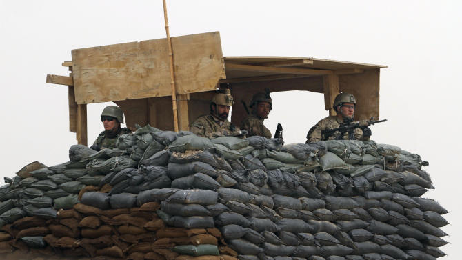 "U.S. Army and Afghan soldiers are seen in a guard tower at their base in Panjwai, Kandahar province south of Kabul, Afghanistan, Sunday, March 11, 2012. Afghan President Hamid Karzai says a U.S. service member has killed more than a dozen people in a shooting including nine children and three women. Karzai called the attack Sunday ""an assassination"" and demanded an explanation from the United States. He says several people were also wounded in the attack on two villages near a U.S. base in the southern province of Kandahar. (AP Photo/Allauddin Khan)"