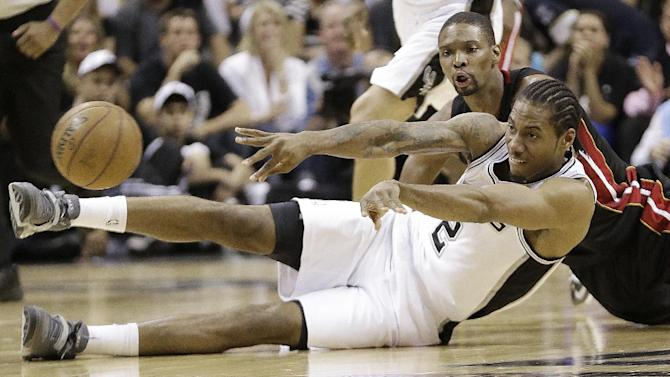 San Antonio Spurs' Kawhi Leonard (2) passes the ball as he and Miami Heat's Chris Bosh hit the floor during the first half at Game 5 of the NBA Finals basketball series, Sunday, June 16, 2013, in San Antonio. (AP Photo/Eric Gay)
