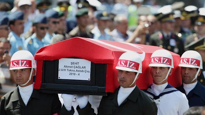 "FILE -In this July 24, 2012 file photo, honour guard soldiers carry the flag-covered coffin of Ahmet Caglar, one of four soldiers killed in fighting Kurdish rebels at Turkey-Iraq border, during his funeral in Ankara, Turkey. Kurdish rebel leader Abdullah Ocalan said Monday, March 18, 2013 that peace talks with Turkey are making ""positive progress"" and that he plans to make a ""historic"" announcement to coincide with a Kurdish spring festival.(AP Photo/Burhan Ozbilici, File)"