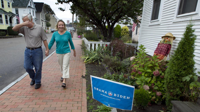 "Joe Galli jokingly covers his face while walking with his wife, Thyra, by an Obama/Biden sign in front of a neighbor's home, Friday, Oct. 5, 2012, in Portsmouth, N.H. New Hampshire's nickname is ""the Granite State"" but there's nothing solid about its political landscape. Independent voters have been the reason in recent presidential elections. Today, former factory towns to the south _ Manchester and Nashua _ typically vote Republican as do the rural small towns up north, while state capital Concord and university towns like Durham, Dover, Keene and Hanover tend to lean Democratic. And the entire state is peppered with independents like Joe and Thyra Galli of Portsmouth. (AP Photo/Robert F. Bukaty)"
