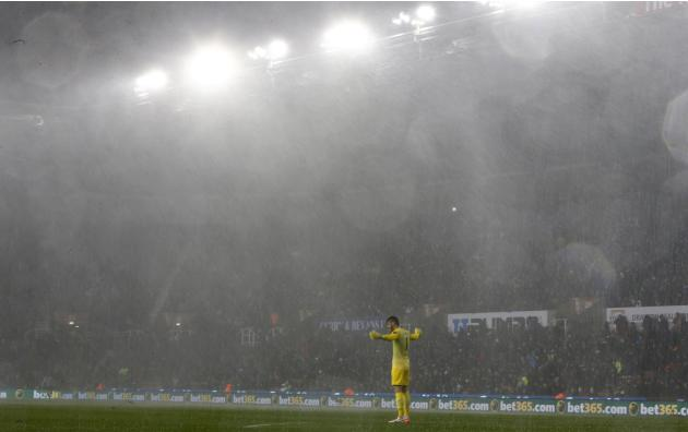 Manchester United's De Gea reacts as play is suspended due to rain during their English League Cup quarter-final soccer match against Stoke City in Stoke-on-Trent