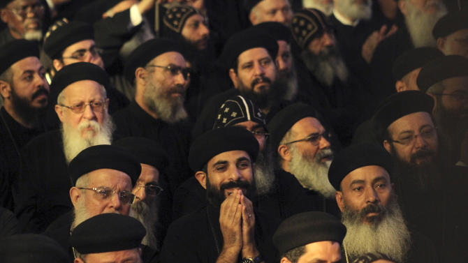 Egyptian Coptic priests participate in the mass enthroning Pope Tawadros II, not shown, during an elaborate ceremony, lasting nearly four hours, attended by the nation's Muslim prime minister and a host of Cabinet ministers and politicians, in the Coptic Cathedral in Cairo, Egypt, Sunday, Nov. 18, 2012. Tawadros II did not address the televised ceremony, but had a brief speech read on his behalf by one of the church's leaders in which he pledged to work for the good of Egypt, with its Muslims and Christians alike. (AP Photo/Roger Anis, El Shorouk Newspaper) EGYPT OUT