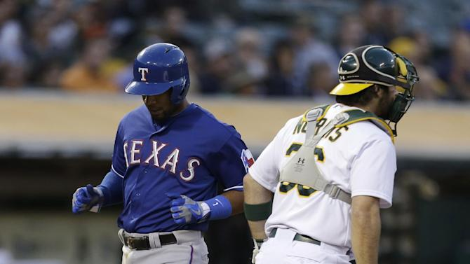 Texas Rangers' Elvis Andrus, left, scores next to Oakland Athletics catcher Derek Norris in the fourth inning of a baseball game Tuesday, May 14, 2013, in Oakland, Calif. (AP Photo/Ben Margot)