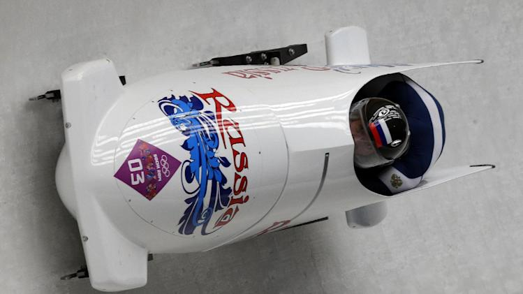 The team from Russia RUS-1, piloted by Alexander Zubkov and brakeman Alexey Voevoda, take a curve during the men's two-man bobsled competition at the 2014 Winter Olympics, Sunday, Feb. 16, 2014, in Krasnaya Polyana, Russia. (AP Photo/Michael Sohn)
