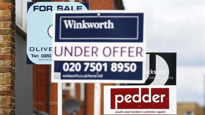 Signs advertising homes, sold, for sale and under offer, are seen on a road in south London