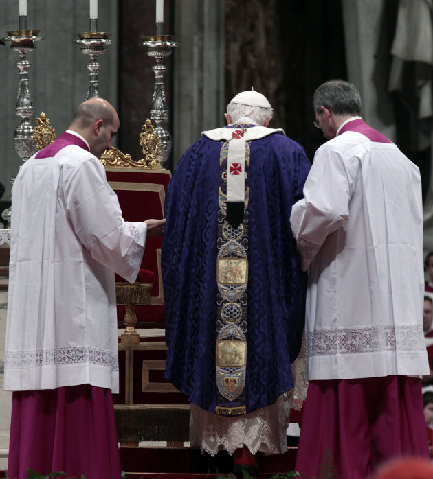 Pope Benedict XVI is helped by master of ceremonies to walk on the altar as he celebrates the Ash Wednesday mass in St. Peter's Basilica at the Vatican, Wednesday, Feb. 13, 2013.  Ash Wednesday marks