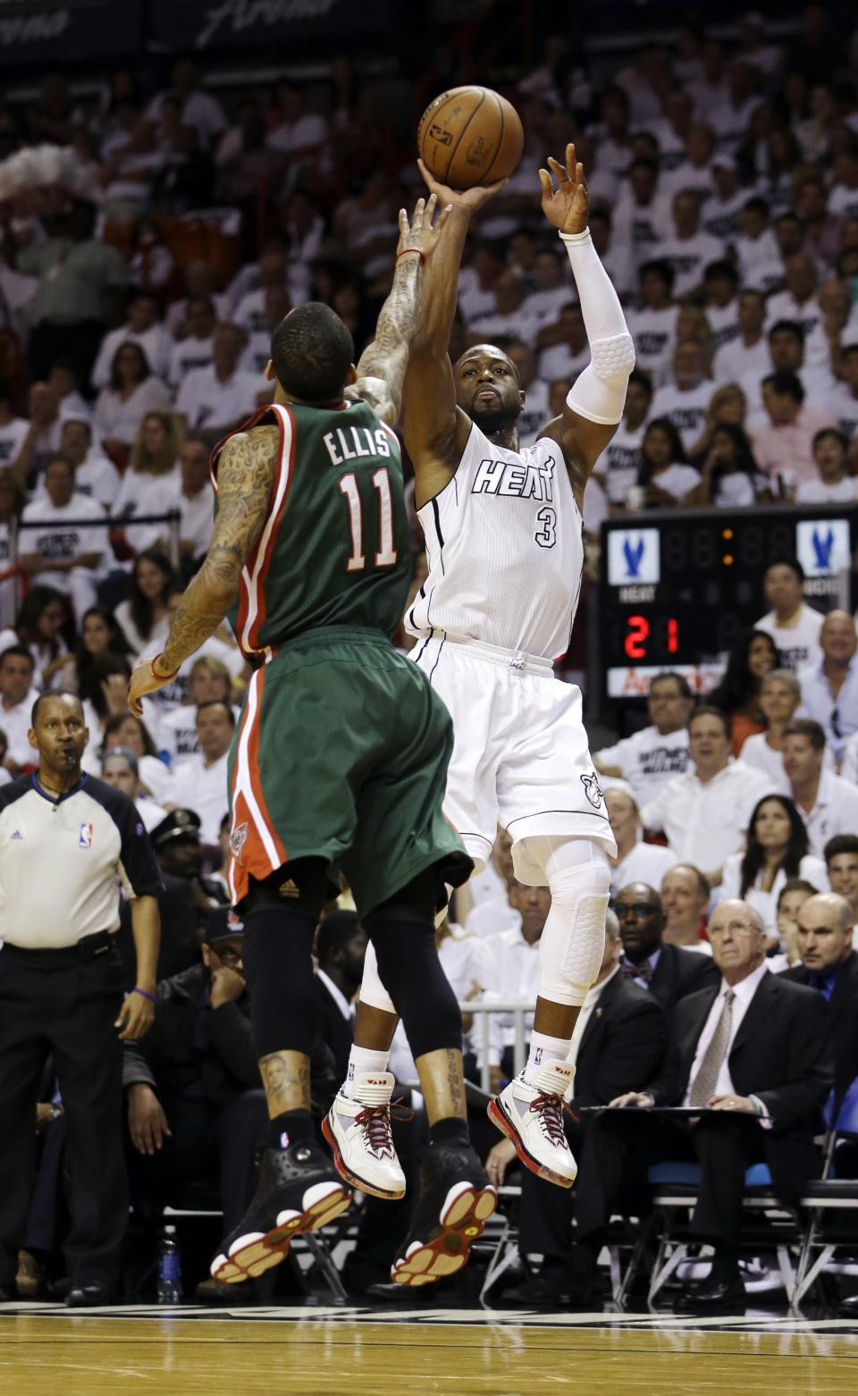 Miami Heat's Dwyane Wade (3) shoots as Milwaukee Bucks' Monta Ellis (11) defends during the first half of Game 1 of their first-round NBA basketball playoff series in Miami, Sunday April 21, 2013. (AP Photo/Alan Diaz)