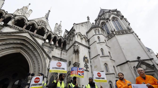 Demonstrators hold banners outside The Royal Courts of Justice in London Friday, Oct. 5, 2012. Babar Ahmad and Syed Talha Ahsan, along with Radical Islamic cleric Abu Hamza al-Masri and two other terror suspects are expected to find out today if they have won their latest legal move to avoid extradition from the UK to America for trial on terrorism charges. (AP Photo/Kirsty Wigglesworth)