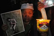 An exiled Tibetan woman holds a photograph of a Tibetan youth, who set himself alight in protest at China's rule, during a candlelight vigil. Four more Tibetans have set themselves alight in protest at China's rule, overseas media and a rights group said Tuesday