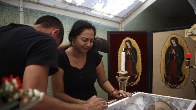 Fernandez and a relative mourn next to the coffin containing the body of her slain husband, during his wake in the town of La Ruana