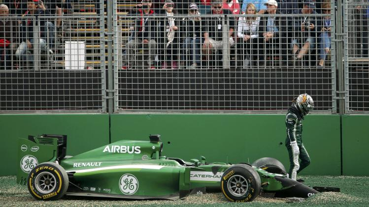 Caterham Formula One driver Kobayashi of Japan stands near his car at the start of the Australian F1 Grand Prix in Melbourne