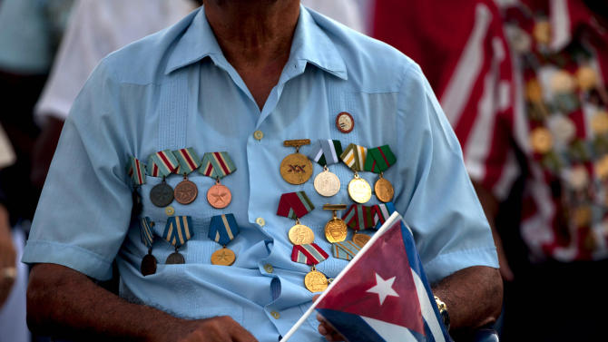 A veteran of the Revolution wears his military medals and holds a Cuban flag at an event celebrating Revolution Day in Guantanamo, Cuba, Thursday, July 26, 2012. Cuba marks the 59th anniversary of the July 26, 1953 rebel attack led by Fidel and Raul Castro on the Moncada military barracks. The attack is considered the beginning of the revolution that culminated with dictator Fulgencio Batista's ouster. (AP Photo/Ramon Espinosa)