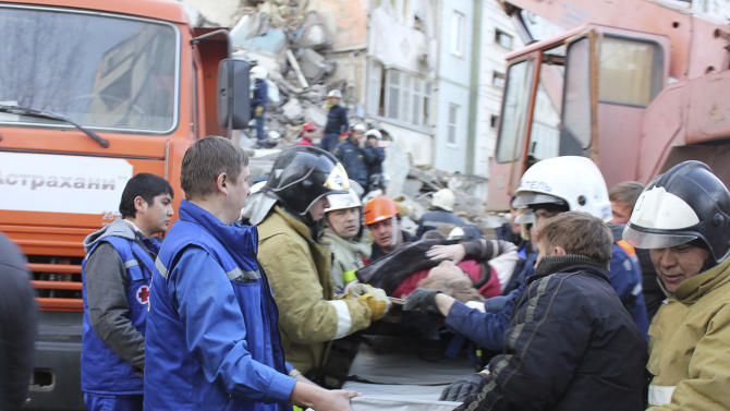 In this photo distributed by Astrakhan branch of the Ministry for Emergency Situations, Emergency Situations Ministry rescuers carry a stretcher with wounded woman near an apartment building after an explosion  on Monday morning, Feb. 27, 2012, in Astrakhan, Russia. Such gas explosions are frequent in Russia.(AP Photo/ Astrakhan Branch, Ministry of Emergency Situations Press Service)