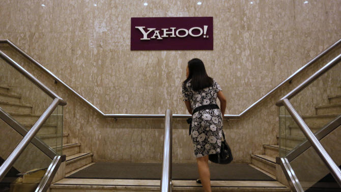 A woman walks up stairs in front of the logo of Yahoo in its Hong Kong office in Hong Kong Monday, May 21, 2012. Struggling Internet company Yahoo Inc. has secured a lifeline after agreeing to sell half of its prized stake in Chinese e-commerce group Alibaba for about $7.1 billion, with most of the cash going to shareholders. (AP Photo/Vincent Yu)