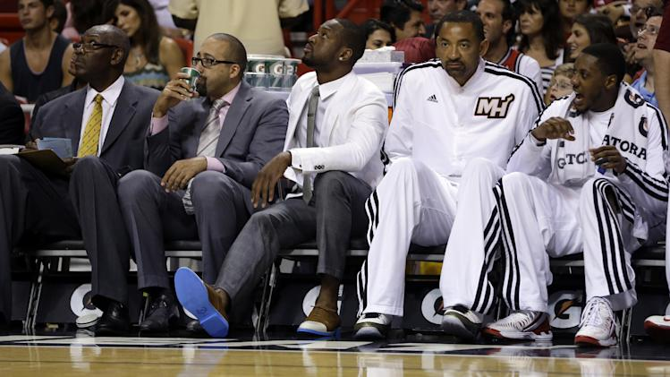 Miami Heat's Dwyane Wade, center, sits on the bench in street clothes because of right knee soreness during an NBA basketball game against the Charlotte Bobcats in Miami, Sunday, March 24, 2013. Juwan Howard, second from right, and Mario Chalmers, right, also sit on the bench. (AP Photo/J Pat Carter)