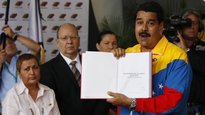 """ADDS REFERENCE TO CHAVEZ'S SIGNATURE - Venezuela's acting President Nicolas Maduro holds up what he says was the government plan created by late President Hugo Chavez, titled """"Homeland Program 2013-2019. Commander Hugo Chavez,"""" with Chavez's signature, after registering his candidacy for president to replace late President Hugo Chavez in Caracas, Venezuela, Monday, March 11, 2013. Behind left stands Tibisay Lucena, president of the national electoral council. Presidential elections were announced to take place on April 14, after the death of Chavez on March 5. (AP Photo/Ariana Cubillos)"""