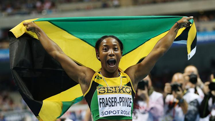 Jamaica's Shelly-Ann Fraser-Pryce carries the national flag after winning the 60m final during the Athletics World Indoor Championships in Sopot, Poland, Sunday, March 9, 2014. (AP Photo/Petr David Josek)