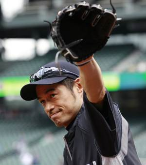 New York Yankees' Ichiro Suzuki waves to fans as he heads onto the field before a baseball game against the Seattle Mariners, Monday, July 23, 2012, in Seattle. The Mariners announced earlier in the day that Suzuki, who has played with the Mariners since 2001, was traded to the Yankees. (AP Photo/Elaine Thompson)