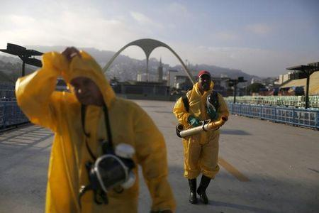 Municipal workers walk after spraying insecticide at Sambodrome in Rio de Janeiro