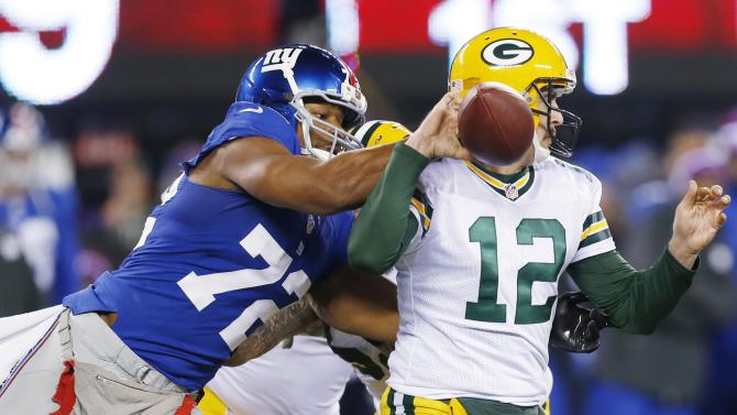 New York Giants defensive end Osi Umenyiora (72) knocks the ball away from Green Bay Packers' Aaron Rodgers (12) during the first half of an NFL football game, Sunday, Nov. 25, 2012, in East Rutherford, N.J. (AP Photo/Julio Cortez)