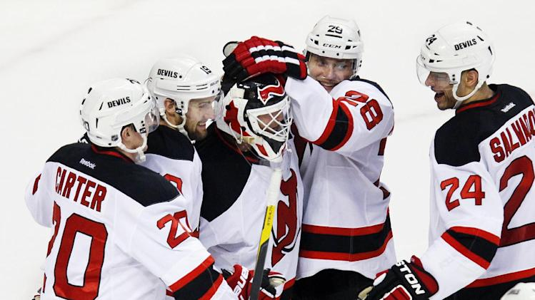 New Jersey Devils goalie Martin Brodeur, center is surrounded by celebrating teammates after they defeated the Philadelphia Flyers 4-1  in Game 2 of an NHL hockey Stanley Cup second-round playoff series Tuesday, May 1, 2012, in Philadelphia. The Devils tied the best of seven series at 1-1.(AP Photo/Tom Mihalek)