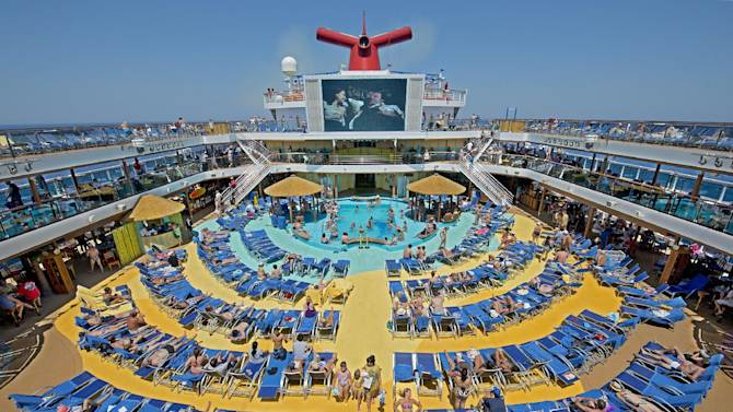 """In this June 23, 2012 photo provided by Carnival Cruise Lines, vacationers aboard the Carnival Breeze enjoy sunbathing at sea while viewing a movie at the Carnival's Seaside Theatre, a lido deck poolside 270-square-foot LED screen offering concerts, sporting events and other programming throughout the day as well as nightly """"Dive In Movies. (AP Photo/Carnival Cruise Lines, Andy Newman)"""