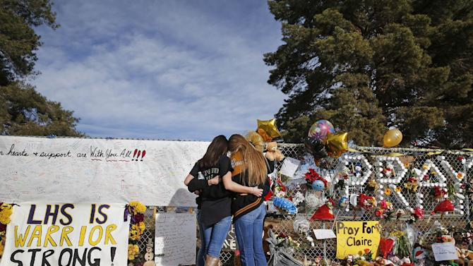 """FILE - In this Dec. 19, 2013 file photo, Arapahoe High School students hug at a tribute site for fatally-wounded student Claire Davis, who was shot by classmate Karl Pierson during a school attack six days earlier at Arapahoe High School, in Centennial, Colo. School disciplinary documents obtained by The Associated Press show that less than a week after Pierson shouted a death threat against his debate coach in a school parking lot, school officials determined that he was """"not a high-level of threat"""" and allowed him to return to his classes. (AP Photo/Brennan Linsley, File)"""