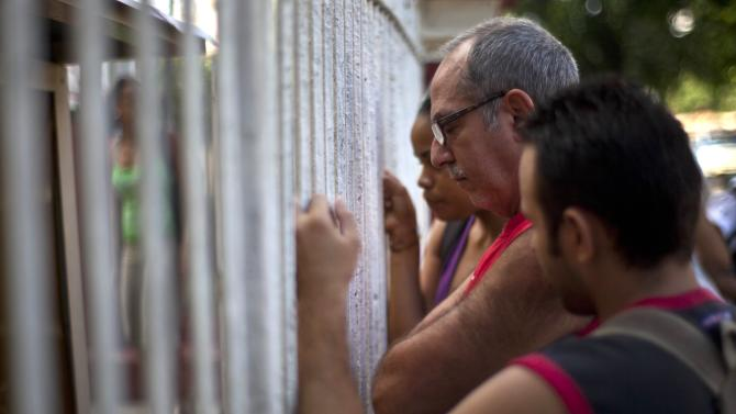 People read adjustments to the migratory policy, posted on a wrought iron fence of an immigration office in Havana, Cuba, Tuesday, Oct. 16, 2012. The Cuban government announced Tuesday that it will no longer require islanders to apply for an exit visa, eliminating a much-loathed bureaucratic procedure that has been a major impediment for many seeking to travel overseas for more than a half-century. (AP Photo/Ramon Espinosa)