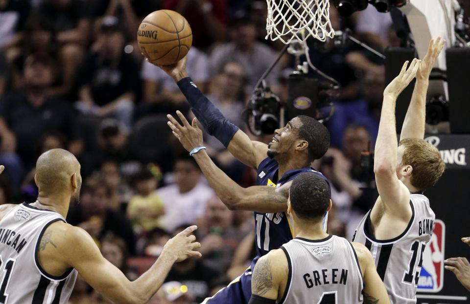 Memphis Grizzlies' Mike Conley (11) shoots as San Antonio Spurs' Tim Duncan, left, Danny Green, and Matt Bonner, right, defend him during the first half in Game 1 of a Western Conference Finals NBA basketball playoff series, Sunday, May 19, 2013, in San Antonio. (AP Photo/Eric Gay)