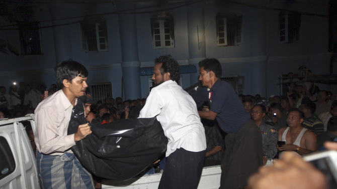 Muslims carry a body bag containing an unidentified victim's body to an ambulance after a fire broke out at a mosque in Yangon, Myanmar, Tuesday, April 2, 2013. Police in Myanmar said 13 children died when an electrical fire broke out at the mosque in the country's largest city. (AP Photo/Khin Maung Win)